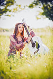 Portrait of pretty young hippie girl with guitar. Outdoor shot