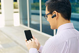 Businessman Calling On Mobile Phone With Bluetooth Handsfree