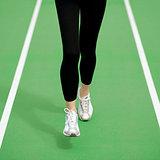 Woman Athlete Runner Feet Running on Green Running Track. Fitness and Workout Wellness Concept.
