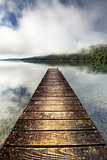 Boat jetty stretching over calm lake with rising mist on the hills, Rotorua, New Zealand