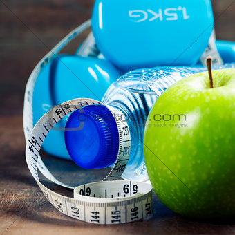 Green apple, dumbbells, water and measuring tape. Health and die