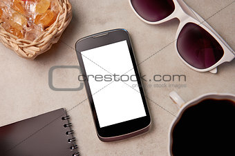 Smartphone, sunglasses, pen and coffee on the table