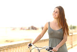 Healthy teen girl walking with a bike in summer