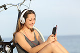Teen girl listening music from a smart phone on the beach