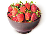 Ripe juicy strawberries in a ceramic bowl top view