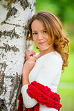 young beautiful girl with red hair in a birch