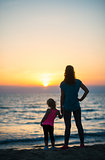 Mother holding daughter's hand at sunset looking out to sea