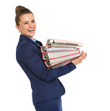Smiling businesswoman in profile holding stack of files