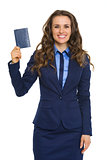 Elegant businesswoman holding up passport and smiling