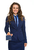 Closeup of businesswoman in suit handing over blue passport