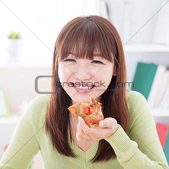Asian girl eating pizza