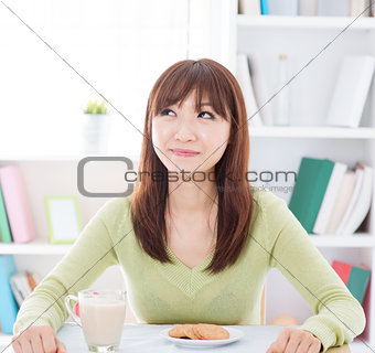 Asian girl eating breakfast and thinking