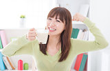 Asian female drinking milk and showing strong arm