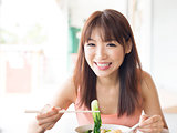 Asian girl eating vegetable noodles