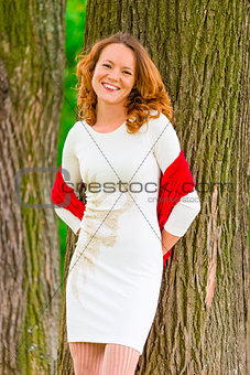 portrait of happy girl near old trees in the park