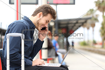 Freelancer working with a laptop and phone in a train station