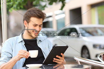 Man reading an ebook or tablet in a coffee shop