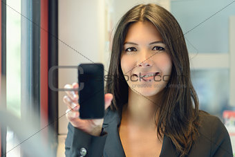 Attractive woman holding up her mobile phone