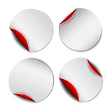 Set of white round promotional stickers with red backside.