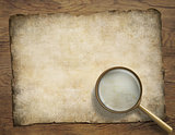 old parchment or map on wooden desk with magnifying glass
