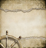 old steering wheel and torn nautical map background