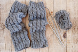 wool grey legwarmers, knitting needles and yarn