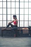 Woman in workout gear choosing workout music in loft gym