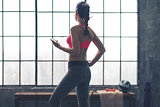 Fit woman standing in gym looking out window listening to music