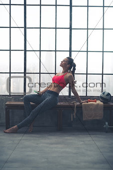 Fit, muscular woman relaxing on bench in loft gym with earbuds