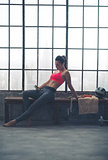 Woman reclining on bench selecting music in loft gym
