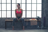 Fit woman sitting on bench in workout gear listening to music