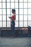 Fit woman selecting music on device in loft gym