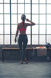 Rear view of fit woman in loft gym listening to music