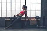 Fit woman in workout gear sitting in profile in loft gym