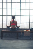 Rear view of woman sitting in lotus position by loft gym window