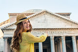 Smiling woman tourist pointing at Pantheon in Rome in summer
