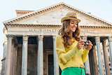 Smiling woman checking photos at the Pantheon in Rome in summer