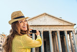 Smiling woman tourist taking photo of Pantheon in Rome