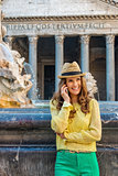 Laughing woman chatting on mobile phone at Pantheon fountain