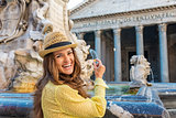 Happy woman tourist preparing coin to throw in Pantheon fountain