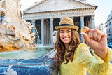 Happy woman tourist holding coin to throw in Pantheon fountain