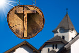 Wooden Cross on Tree Trunk with Church
