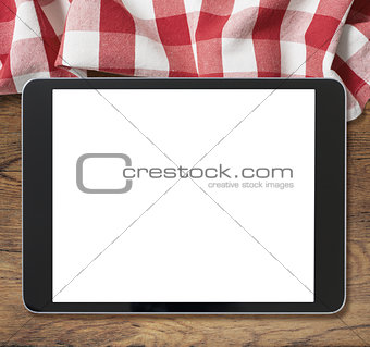 black tablet pc on wooden table and picnic tablecloth