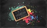 Slate in wooden frame, piece of chalk on black background with colorful splatters
