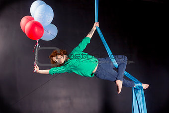 Beautitul girl with balloons on aerial silk