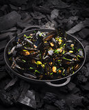 Steamed Mussels with vegetables in a black frying pan on the coa