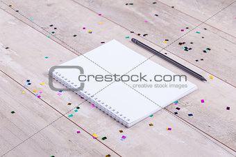Blank notepad and pencil on the wooden table