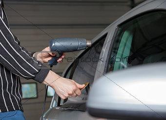 Applying tinting foil on a car window