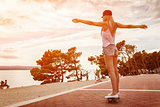Young carefree woman riding a skateboard along the coast