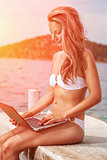 Woman sitting and relaxing on a beach with a laptop